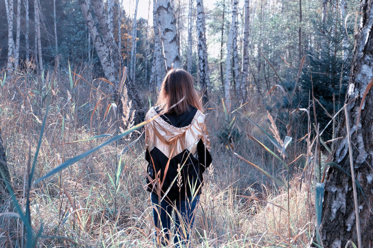 Rear view of young woman standing in forest