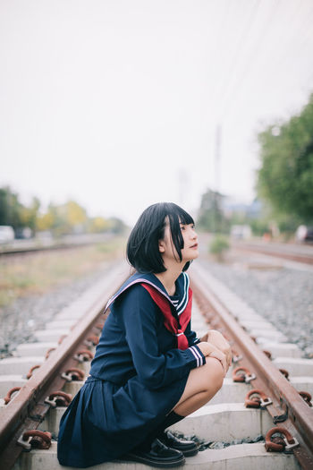 Woman looking away while sitting on railroad track against clear sky