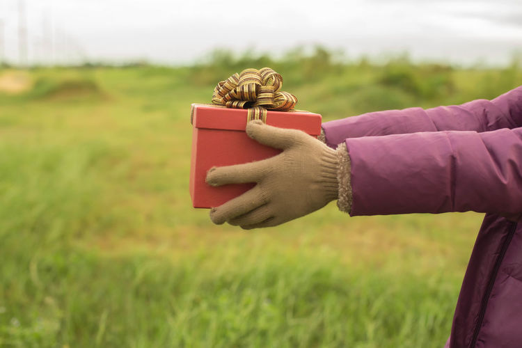 Woman holding gift box on field