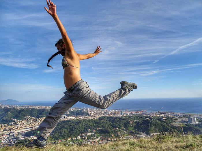 Energetic woman leaping in mid-air against sky