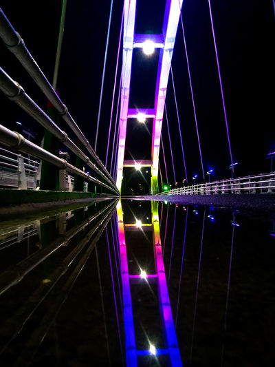 Illuminated bridge in city at night