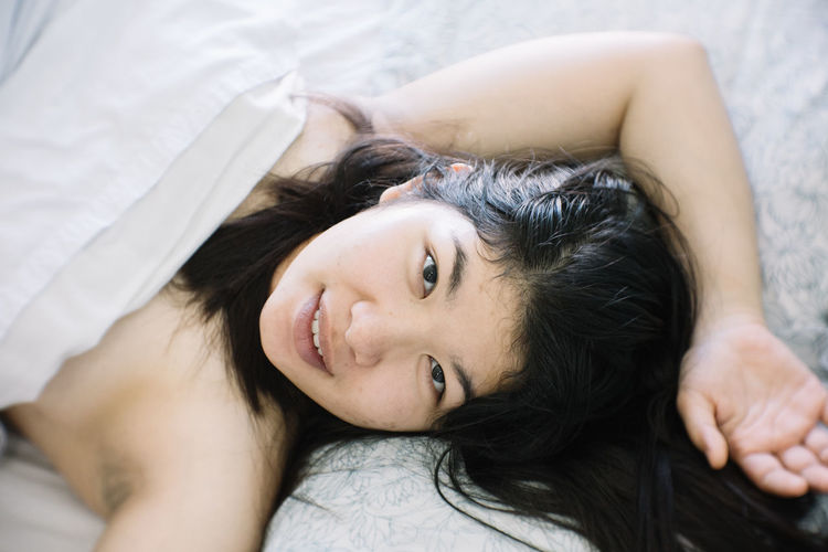 Lying Down Furniture Relaxation Portrait Bed One Person Women Smiling Young Adult Looking At Camera Lying On Back Headshot High Angle View Indoors  Happiness Beautiful Woman Black Hair Hair Adult Beauty Hairstyle Human Arm Cozy Hands Behind Head