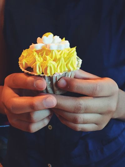 Midsection of person holding cupcake