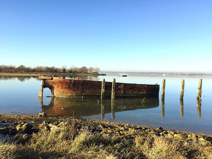 Old boat moored by wooden posts in lake against clear blue sky