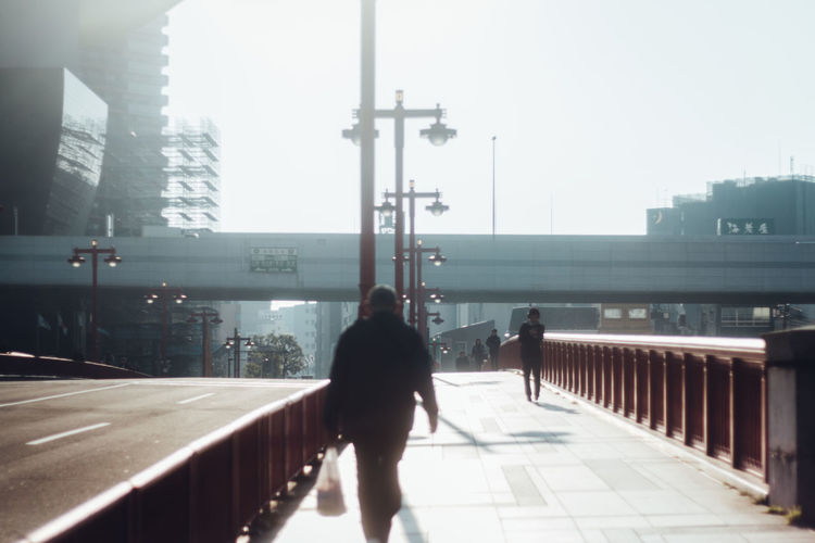 Walk This Way From My Point Of View Japan Morning Silhouette Sky And City Snapshots Of Life The Week On EyeEm Tokyo Architecture Built Structure City Day Full Length Getting Inspired Light And Shadow Men Looking Into The Future Outdoors People Railing Shaping The Future. Together. Rear View Walking The Week Of Eyeem