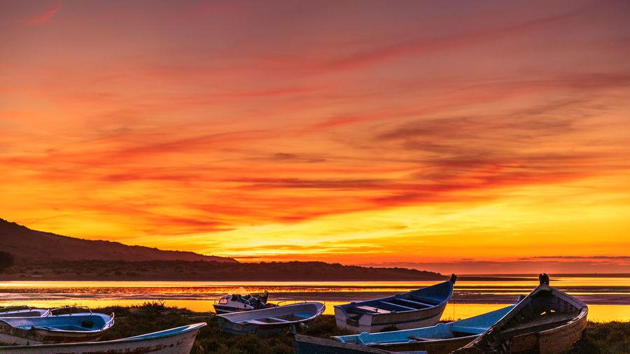 Boats moored in sea against orange sky