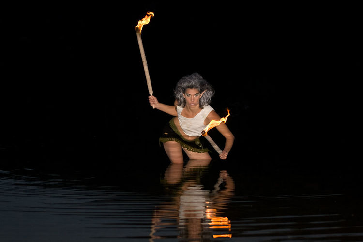 Portrait of woman with burning sticks in lake