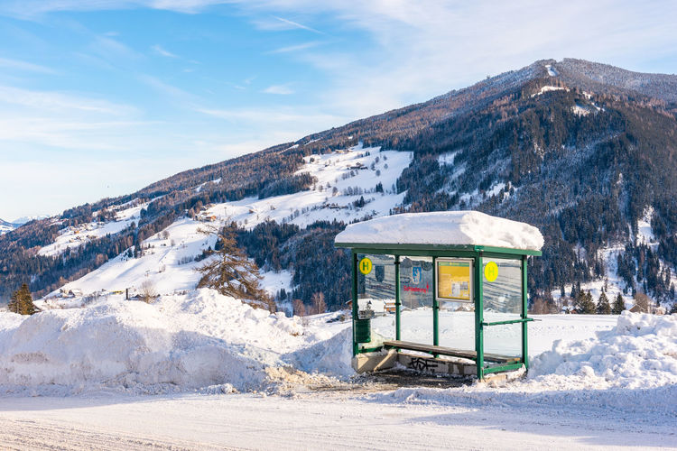 Ski bus stop at austria. scenic view of snowcapped mountains against sky.