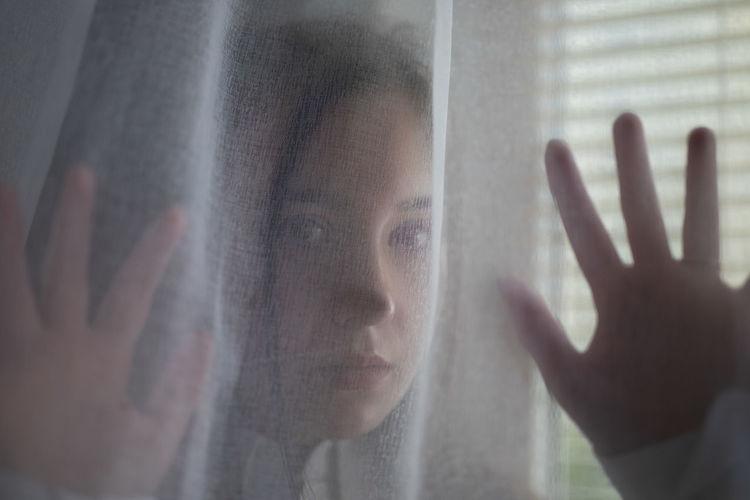 Portrait of hand touching glass window