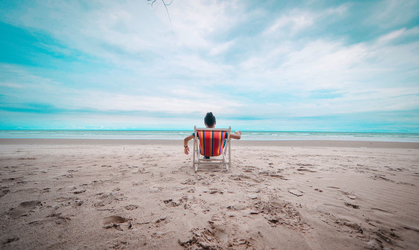 Rear view of man relaxing on beach against sky