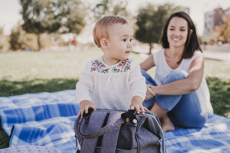 Mother and daughter sitting on picnic blanket at park