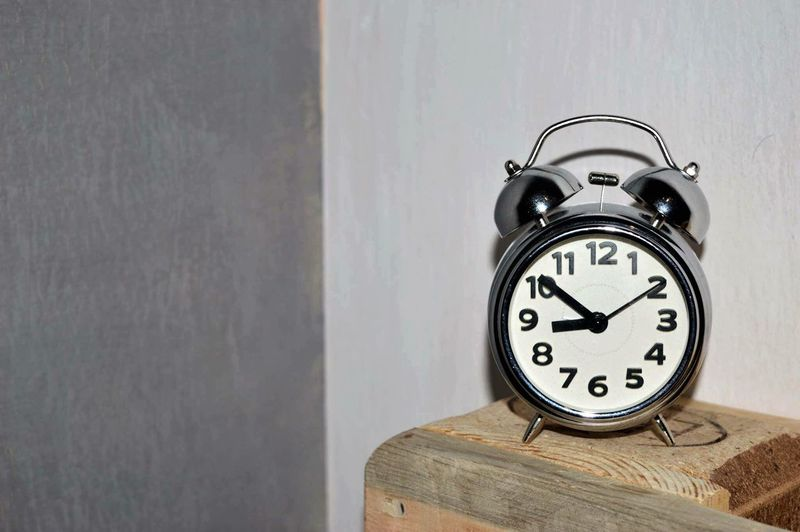 Close-up of alarm clock on wooden table against wall