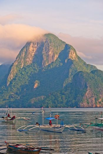 Palawan Philippines Nautical Vessel Water Transportation Mountain Mode Of Transportation Beauty In Nature Scenics - Nature Sky Nature Sea Mountain Range Moored Day Waterfront Cloud - Sky Tranquility Travel Group Of People Tranquil Scene Outdoors Palawan Philippines Cloudy Mountain Peaks Boat Resort Sunset