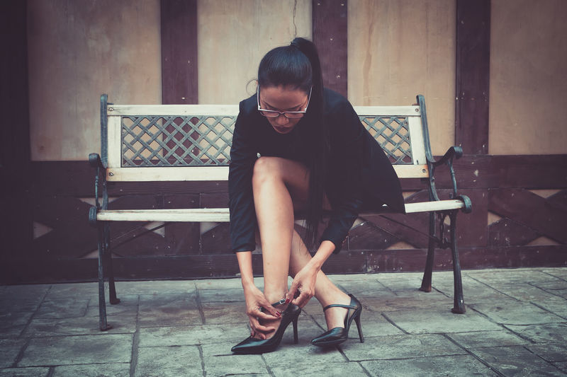 Mid adult woman adjusting sandal while sitting on bench