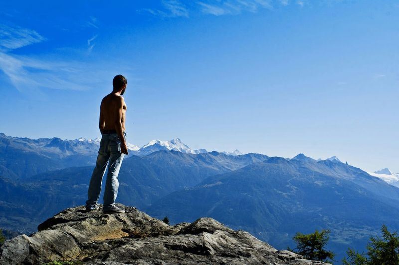 Rear view of shirtless man standing on mountain against sky
