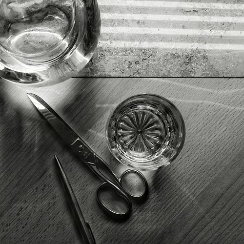 High angle view of scissor and glass on wooden table