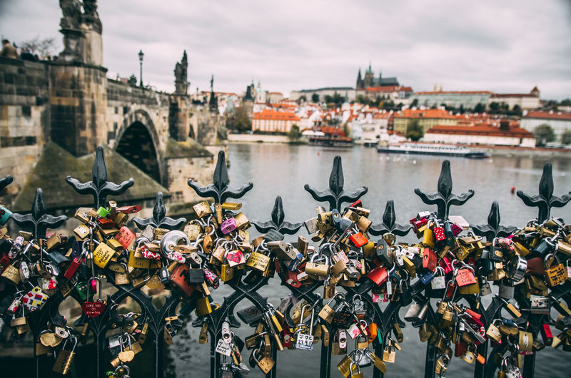 Close-Up Of Padlocks On Bridge Over River Against Cloudy Sky In City