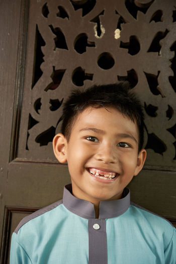Portrait of malay boy in malay traditional cloth on against wooden craving background