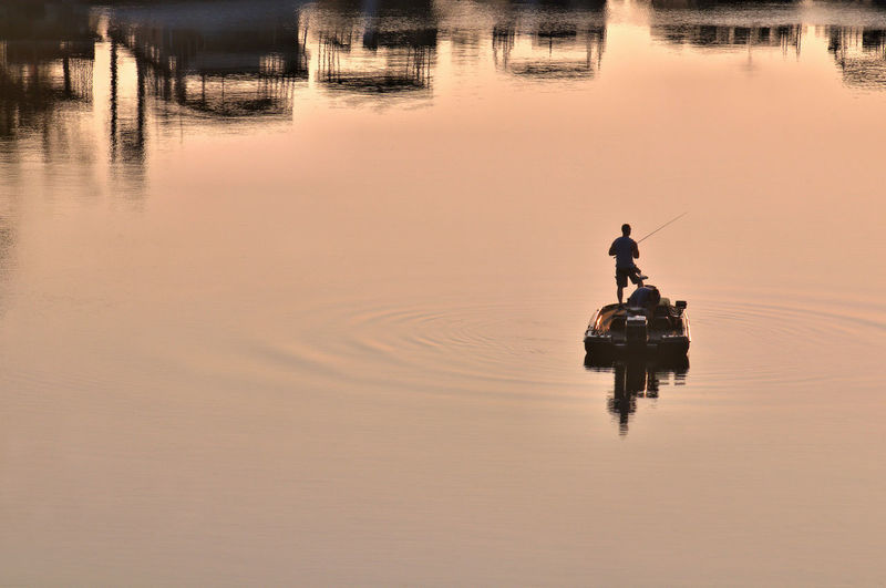Rear view of man fishing in lake