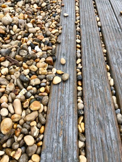Deck boards Natural Man-made Wood Against Stone Beach Pattern, Texture, Shape And Form Pebbles