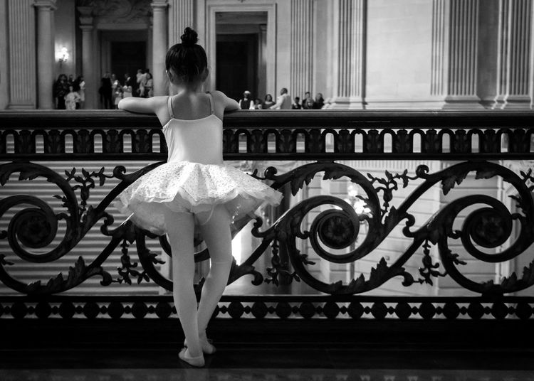 Rear view of ballerina standing against railing