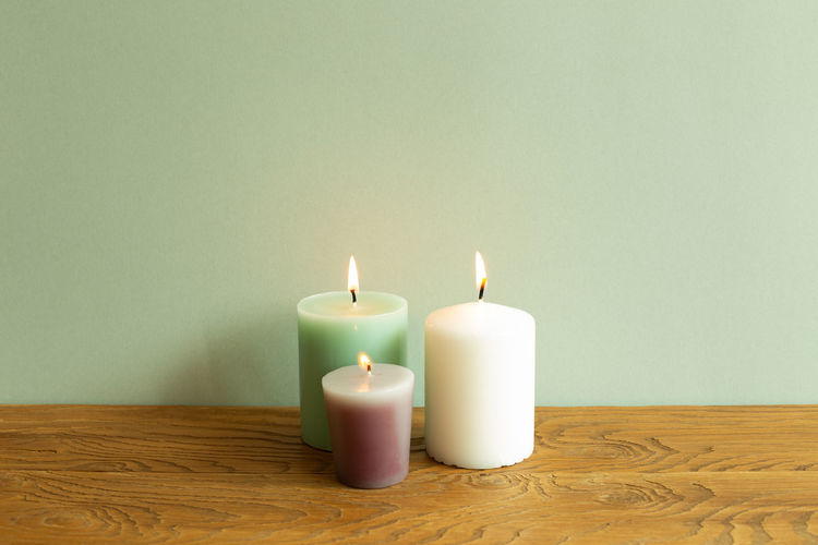 Close-up of lit candles on table against wall