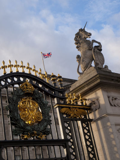"Buckingham Palace Gates Located in the City of Westminster, the palace is often at the centre of state occasions and royal hospitality. It has been a focal point for the British people at times of national rejoicing and mourning.Originally known as Buckingham House, the building at the core of today's palace was a large townhouse built for the Duke of Buckingham in 1703 on a site that had been in private ownership for at least 150 years. It was acquired by King George III in 1761 as a private residence for Queen Charlotte and became known as ""The Queen's House"". During the 19th century it was enlarged, principally by architects John Nash and Edward Blore, who constructed three wings around a central courtyard. Buckingham Palace became the London residence of the British monarch on the accession of Queen Victoria in 1837. Architecture Astrology Sign Buckingham Palace Built Structure Cloud - Sky Coat Of Arms Cultures Day Gold Gold Colored No People Outdoors Representing Sculpture Sky Statue Tourist Attraction  Travel Travel Destinations Traveling Vivid International Wrought Iron"