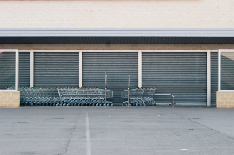 Closed, empty entry of supermarket and with cars of the purchase piled up