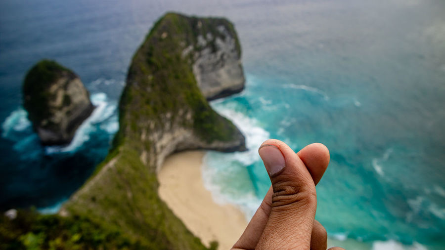 the famous kelingking nusa penida bali Water Sea Nature Day Outdoors Human Body Part Human Hand Hand One Person Body Part Unrecognizable Person Rock Personal Perspective Real People Solid Leisure Activity Rock - Object Finger Marine Dinosaur Beach Ocean Green Color Blue Nature Frame