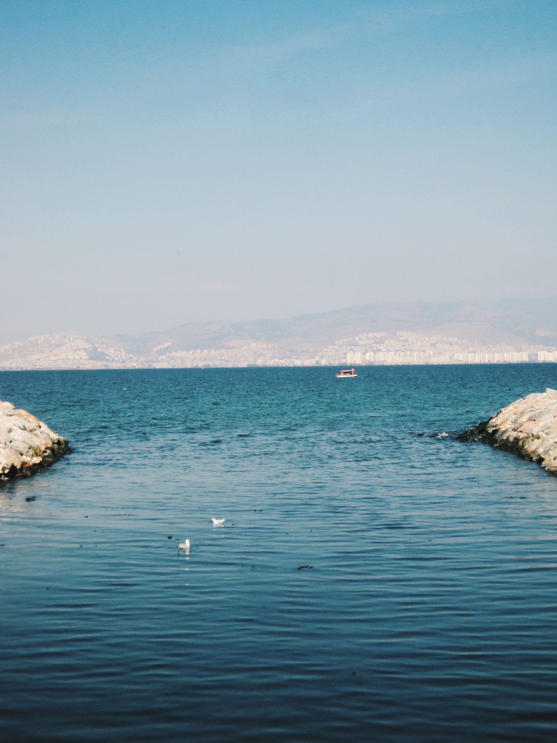 water, sea, tranquil scene, clear sky, scenics, tranquility, copy space, beauty in nature, blue, waterfront, nature, idyllic, rippled, horizon over water, mountain, day, rock - object, outdoors, no people, non-urban scene