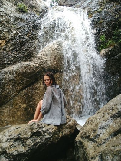 Portrait of young woman sitting on rock against waterfall
