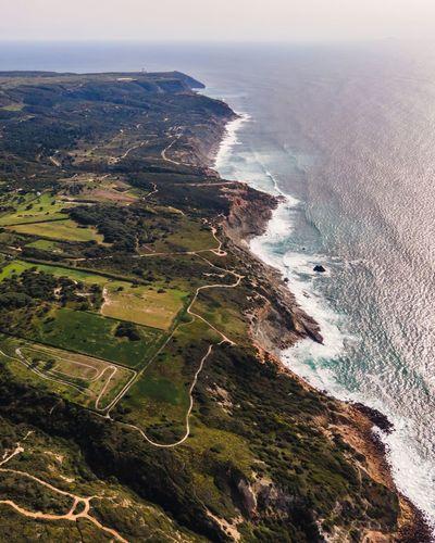 Aerial view of wild coastline with atlantic ocean waves rolling on the cliffs near praia da foz