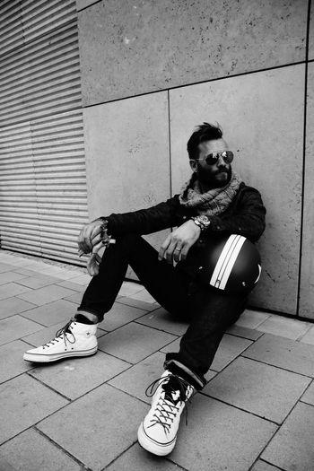Portrait of young man sitting on sidewalk