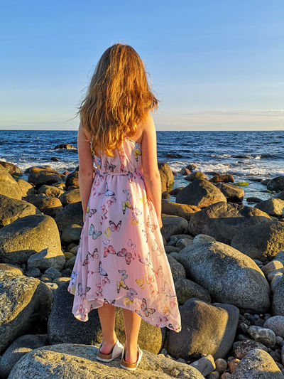 Rear view of woman looking at sea shore against sky