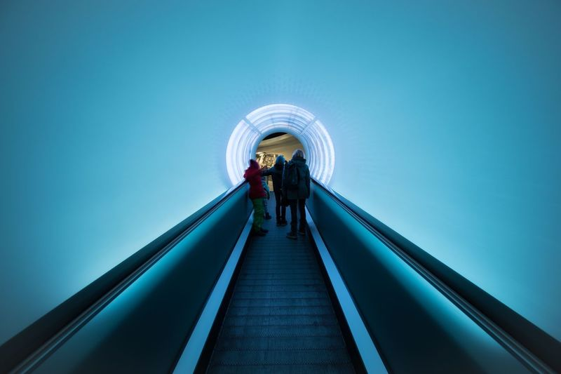 People standing on moving walkway in building