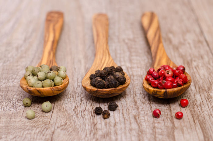 Red, black and green peppercorns on wooden spoons Green Color Peppercorns Red Black Close-up Day Dried Fruit Food Food And Drink Freshness Fruit Healthy Eating Indoors  Ingredient No People Rustic Spoons Still Life Studio Shot Variation Wood - Material Wooden Spoon