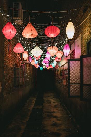Illuminated lanterns hanging by building at night