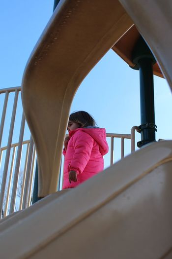 Low angle view of girl on slide in park