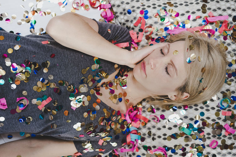 High angle view of woman relaxing with multi colored decorations on bed