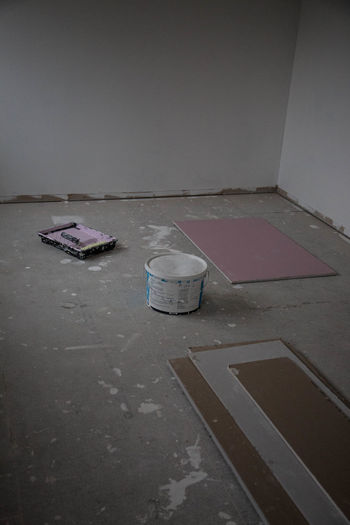 High angle view of abandoned paper on table against wall