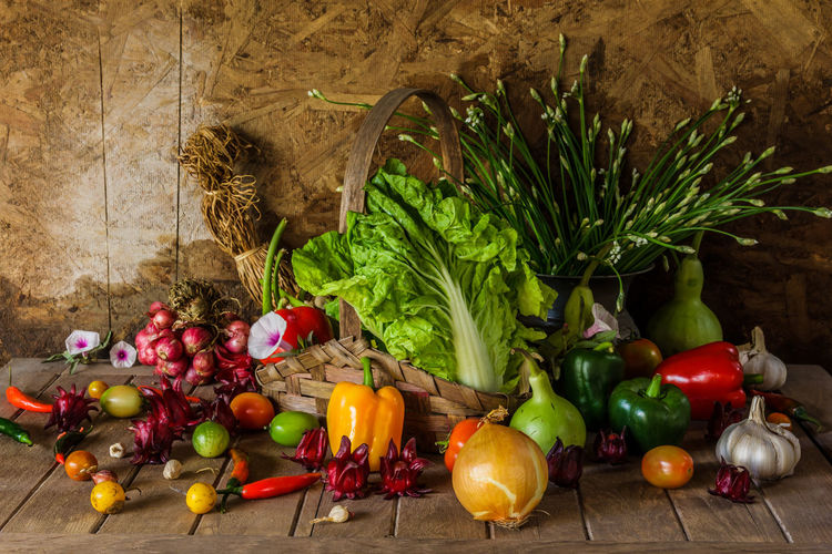 Still life with vegetables, herbs and fruits are beautifully placed on the wooden floor.