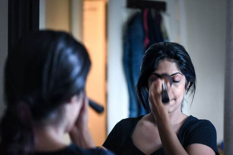 Reflection of woman applying blusher on face in mirror at home