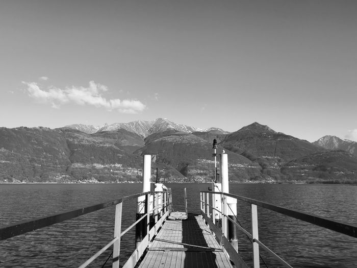 Pier leading towards mountains against sky