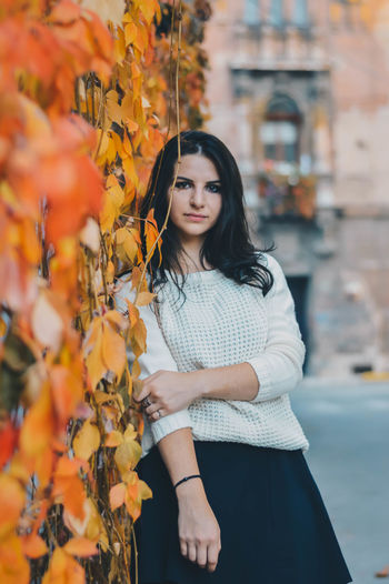 Young woman standing by plants on wall