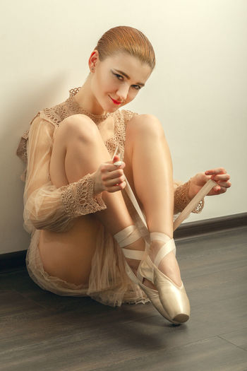 Portrait of ballerina wearing ballet shoes while sitting on floor