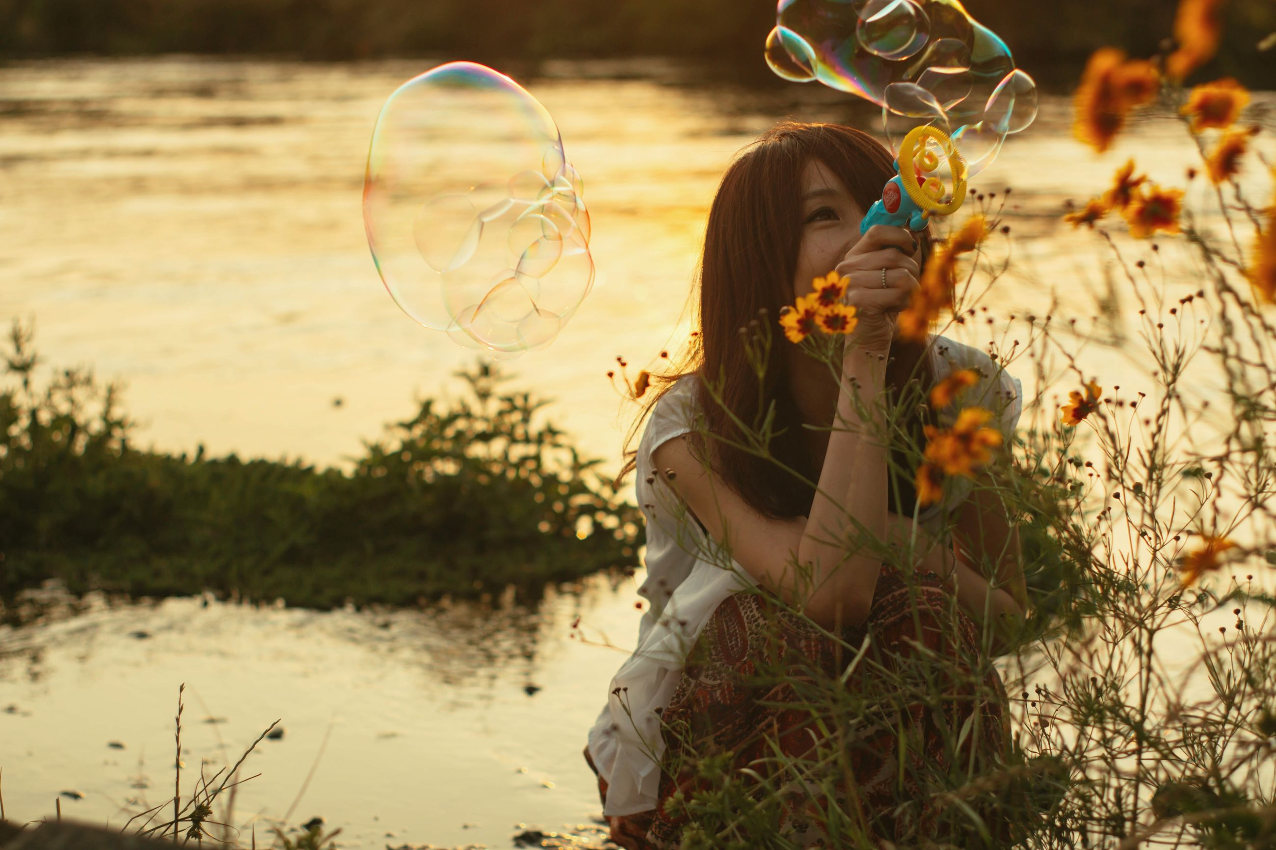 real people, one person, leisure activity, holding, lifestyles, outdoors, young women, front view, casual clothing, bubble wand, young adult, full length, standing, nature, beautiful woman, fragility, day, water, women, flower, people