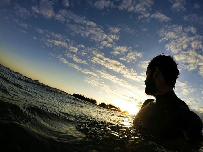 Tilt Image Of Man In Sea Against Sky During Sunset