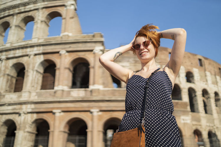 Young woman standing against historic building