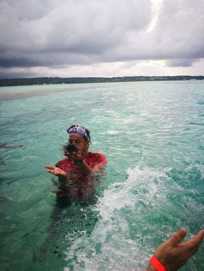 Man holding sea urchin while swimming in sea against sky