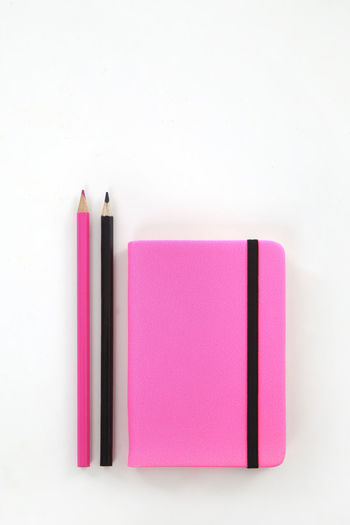 Directly above shot of pink book against white background